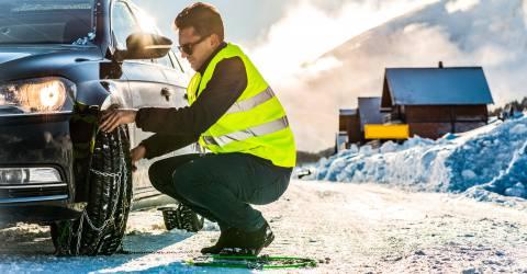 Man legt sneeuwketting aan op z'n auto